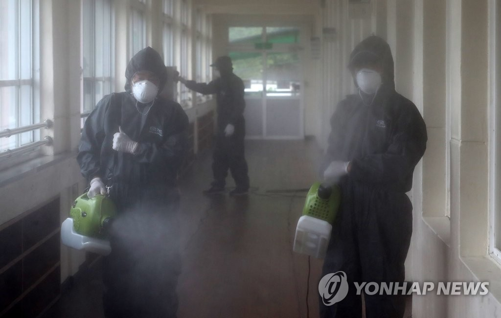 Quarantine officials disinfect an elementary school in Daejeon, 164 kilometers south of Seoul, on June 30, 2020, as one of its students tested positive for the new coronavirus. (Yonhap)