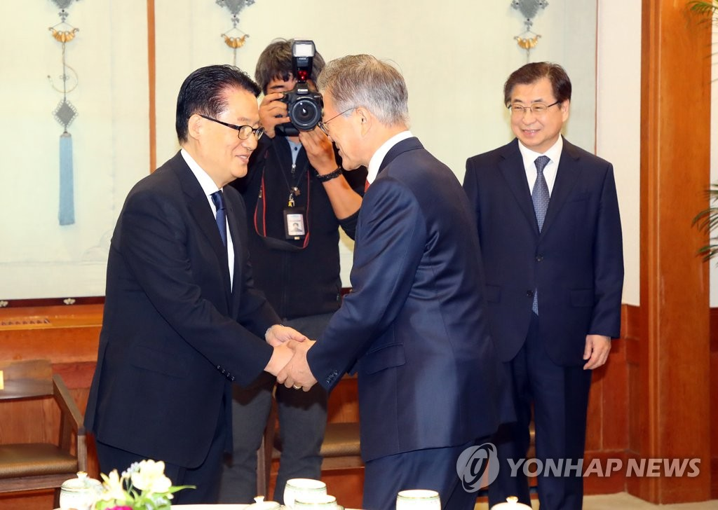 This file photo shows former lawmaker Park Jie-won (L) shaking hands with President Moon Jae-in at Cheong Wa Dae. (Yonhap)