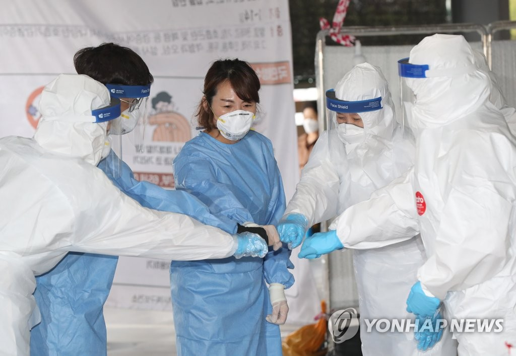 Before conducting new coronavirus tests, health workers bump fists at a screening center in Gwangju, 329 kilometers southwest of Seoul, on July 14, 2020. (Yonhap)