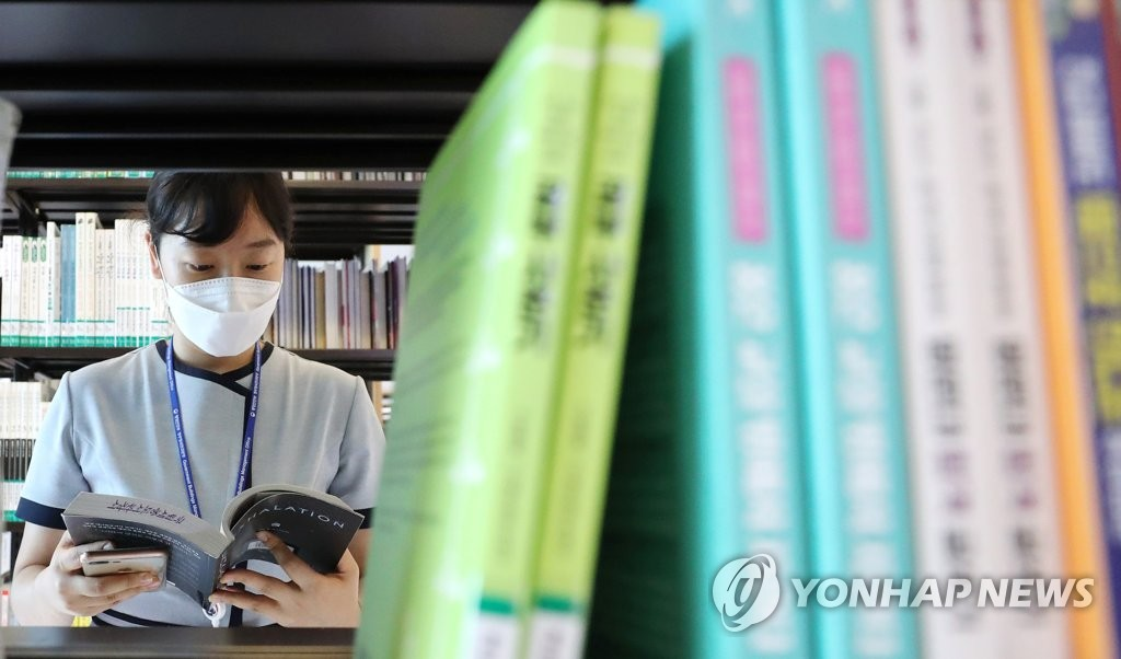 A visitor wearing a protective mask reads a book at the National Library of Korea in Sejong, central South Korea, on July 22, 2020. (Yonhap)