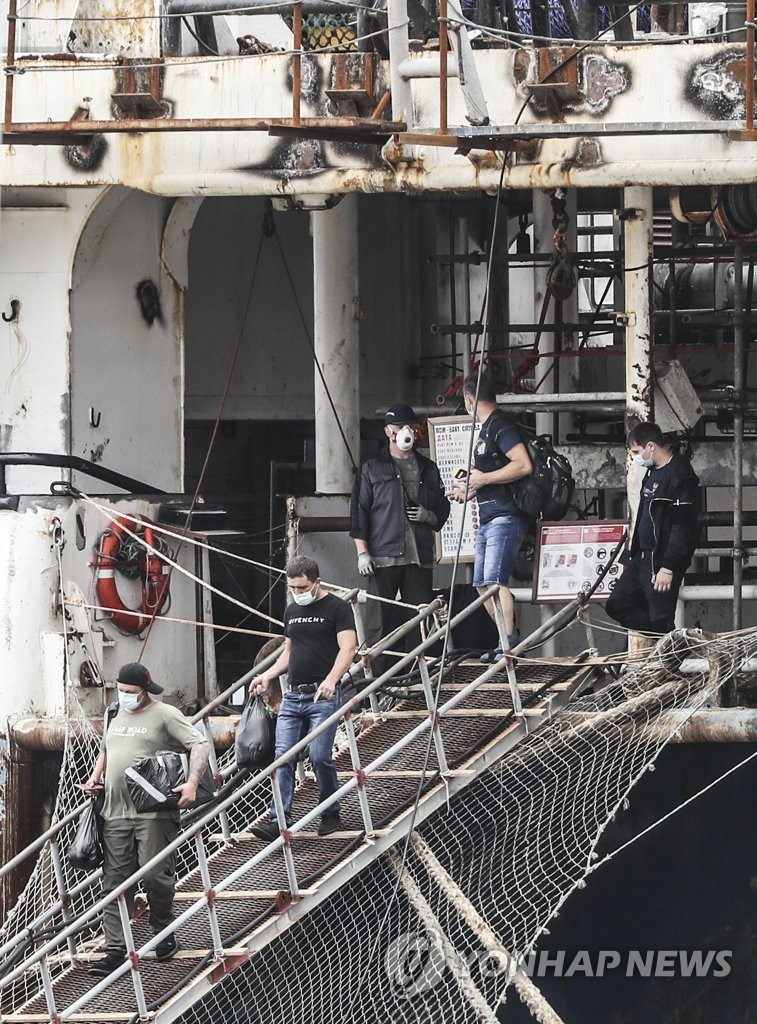 Crew members of a 7,733-ton Russian pelagic fishing boat get off the ship to be transported to Busan Medical Center in Busan on July 24, 2020. Of the 92 crewmen, 32 tested positive for COVID-19. (Yonhap)