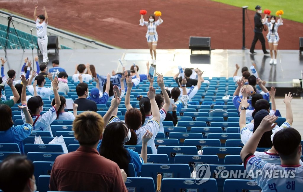 In this file photo from July 29, 2020, fans of the Samsung Lions follow their cheerleaders while rooting for the home team against the Hanwha Eagles during a Korea Baseball Organization regular season game at Daegu Samsung Lions Park in Daegu, 300 kilometers southeast of Seoul. (Yonhap)