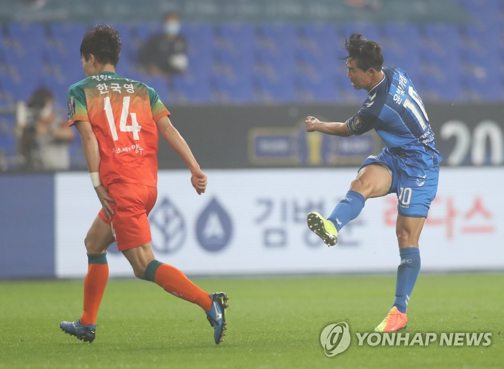 Yoon Bitgaram of Ulsan Hyundai FC (R) takes a shot past Han Kook-young of Gangwon FC during their quarterfinals match at the Korea Football Association Cup at Ulsan Munsu Football Stadium in Ulsan, 415 kilometers southeast of Seoul, on July 29, 2020. (Yonhap)
