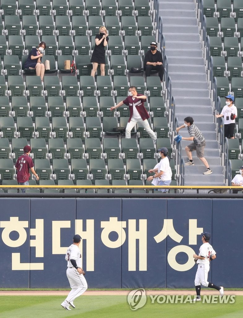 In this file photo from July 30, 2020, fans chase a home run ball hit by Park Dong-won of the Kiwoom Heroes during a Korea Baseball Organization regular season game against the Doosan Bears at Jamsil Baseball Stadium in Seoul. (Yonhap)