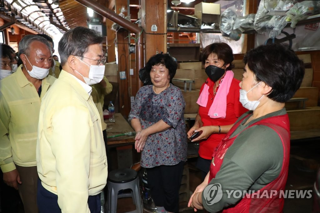 President Moon Jae-in (R) talks with merchants at Hwagae Market in Hadong, South Gyeongsang Province, which suffered damage caused by heavy rains, on Aug. 12, 2020. (Yonhap)