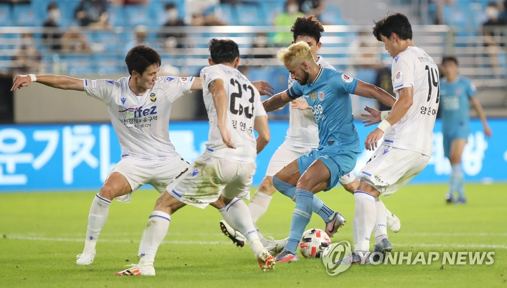 In this file photo from Aug. 16, 2020, Cesinha of Daegu FC (C, in blue) is surrounded by Incheon United players during their K League 1 match at DGB Daegu Bank Park in Daegu, 300 kilometers southeast of Seoul. (Yonhap)