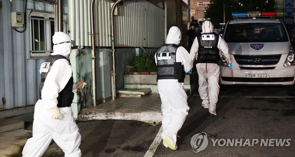 Police officers wearing protective gear head toward Sarang Jeil Church in Seoul on Aug. 21, 2020, for a search and seizure operation. A court issued a warrant after health authorities failed to secure the full list of the members of the church at the center of recent spikes in coronavirus infections in the country. (Yonhap)