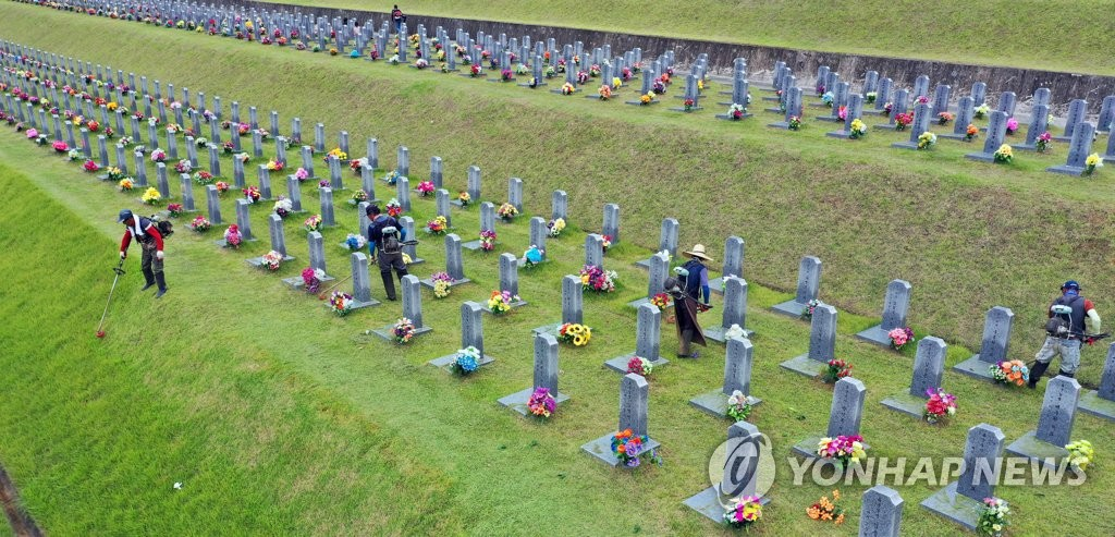 Workers cut grass at Yeongcheon National Cemetery in Yeongcheon, North Gyeongsang Province, on Sept. 18, 2020, ahead of the Chuseok holiday. Mowing grass around the tombs is part of Koreans' preparations for the traditional holiday, which falls on Oct. 1 this year. (Yonhap)