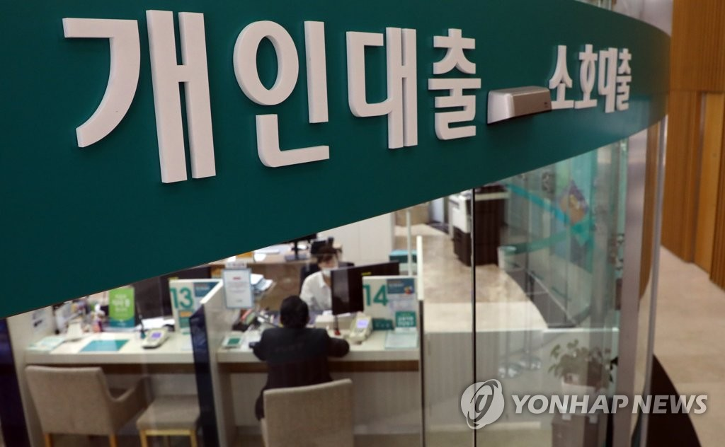 This photo, taken on Sept. 18, 2020, shows a bank official explaining loan products to a customer at a branch in Seoul. (Yonhap)