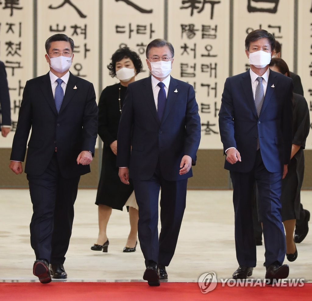 President Moon Jae-in (C) walks toward a Cheong Wa Dae room to converse with Defense Minister Suh Wook (L) and the National Tax Service Commissioner after presenting them with certificates of appointment on Sept. 18, 2020. (Yonhap)