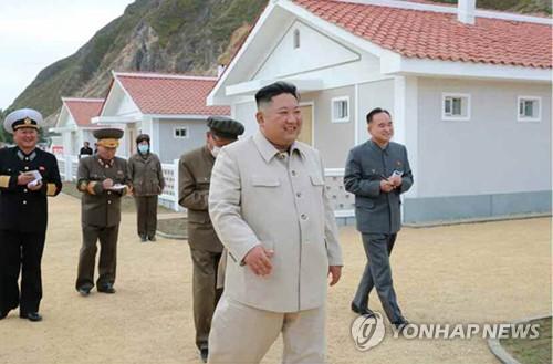 태풍 피해지역에 새로 지은 주택을 돌아보며 환히 웃는 김정은
