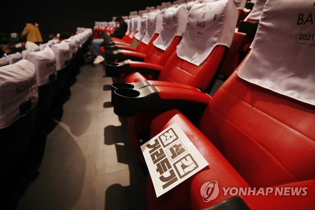 This file photo taken on Oct. 28, 2020, shows signs urging social distanced seating at a movie theater in Seoul. (Yonhap)