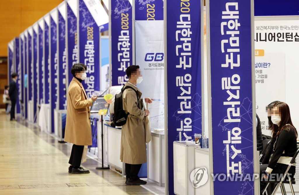 In this file photo taken Nov. 11, 2020, jobseekers look around booths of a job fair in the Convention and Exhibition Center in southern Seoul. (Yonhap)