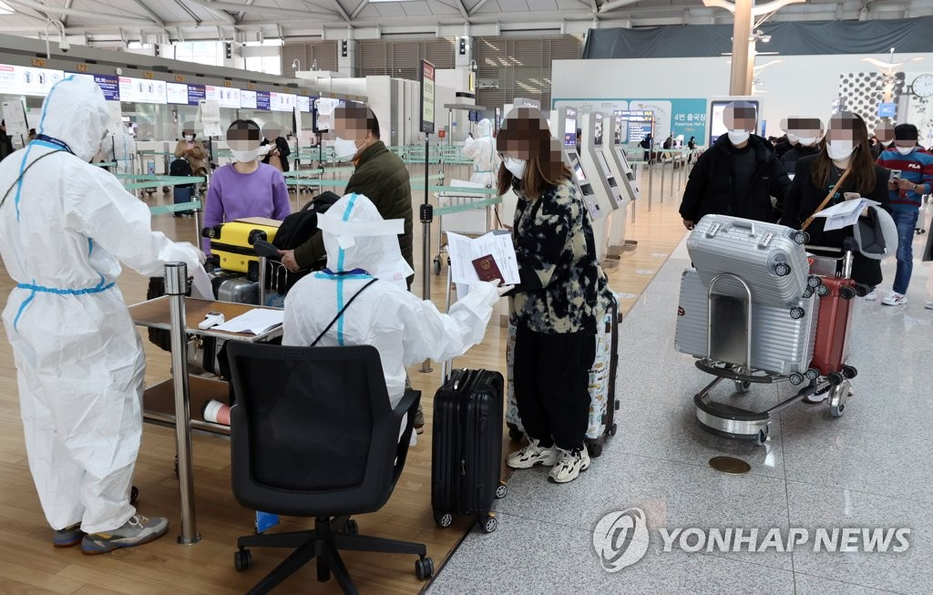 Airport officials assist travelers at Incheon International Airport, west of Seoul, on Nov. 11, 2020. (Yonhap)