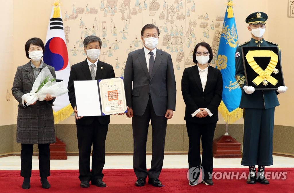 President Moon Jae-in (C) poses with family members of the late labor activist Chun Tae-il after posthumously conferring on him the Mugunghwa Medal of the Order of Civil Merit during a ceremony at Cheong Wa Dae in Seoul on Nov. 12, 2020. Flanking Moon from left to right are Chun's younger sister, Tae-ri, younger brother, Tae-sam, and younger sister, Soon-ok. (Yonhap)
