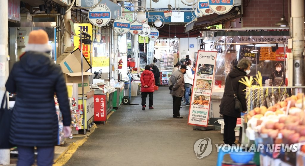 This file photo, taken Dec. 12, 2020, shows people shopping for groceries at a traditional market in western Seoul. (Yonhap)