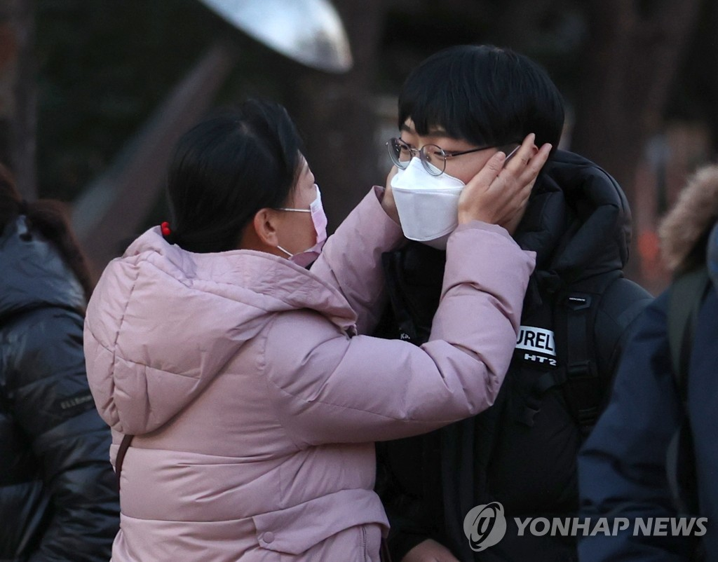 A mother encourages her son at the gate of a high school in Seoul as the student enters the school to take the college entrance exam on Dec. 3, 2020. (Yonhap)
