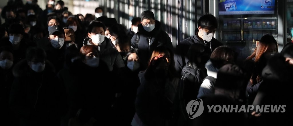 Commuters wearing protective masks walk at a subway station in western Seoul on Dec. 14, 2020. (Yonhap)