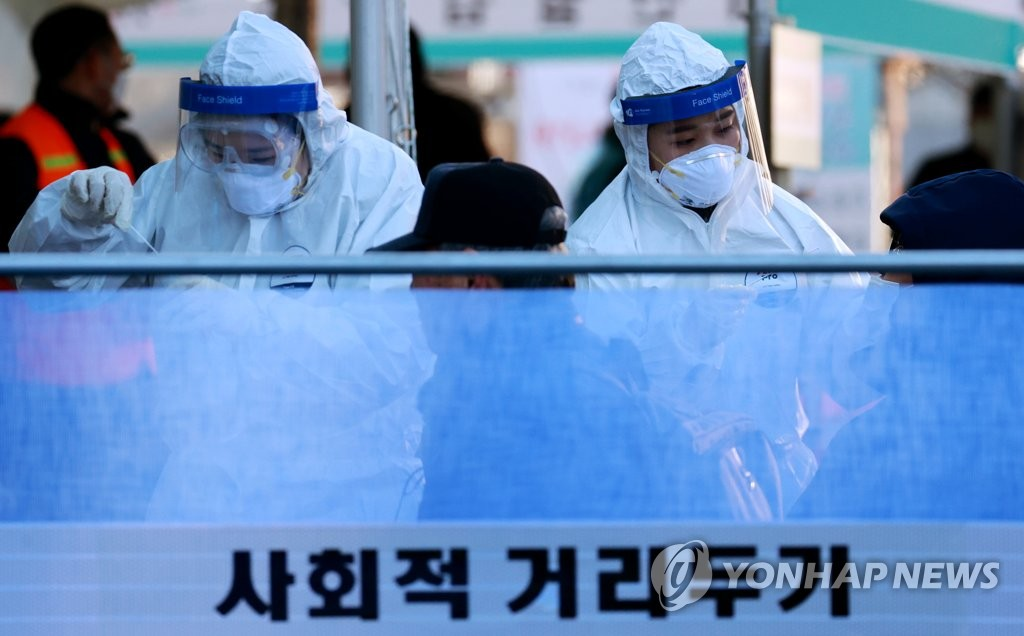 Medical workers collect specimens from people for COVID-19 testing at a temporary screening station in front of Seoul Station on Dec. 16, 2020. (Yonhap)