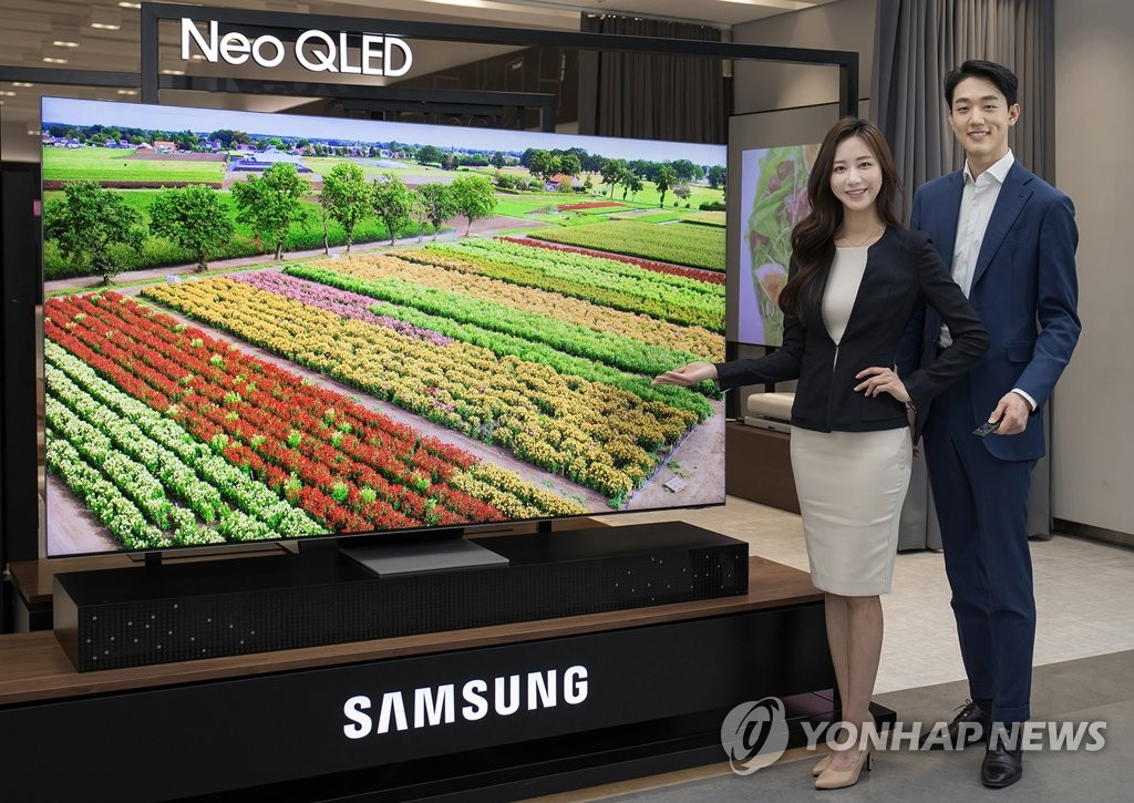This photo provided by Samsung Electronics Co. on Jan. 7, 2021, shows models posing for a photo with the company's Neo QLED TV that used Mini LED technology. (PHOTO NOT FOR SALE) (Yonhap)