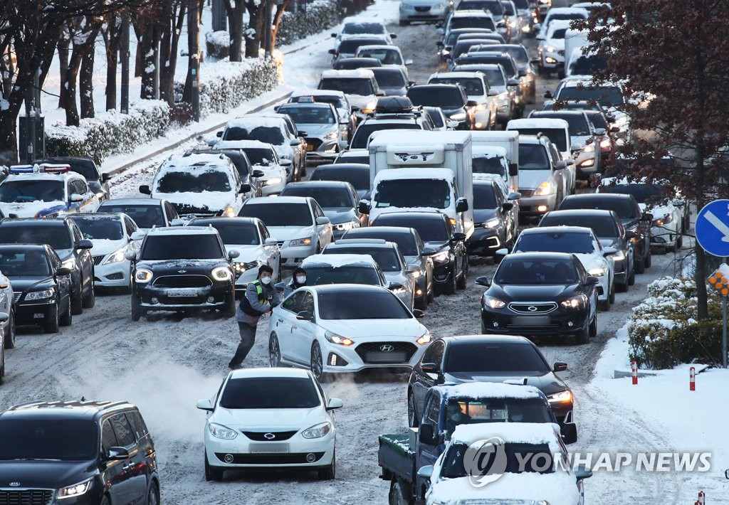 Cars move slowly on a snow-covered road in Suwon, just south of Seoul, on Jan. 7, 2021. (Yonhap)