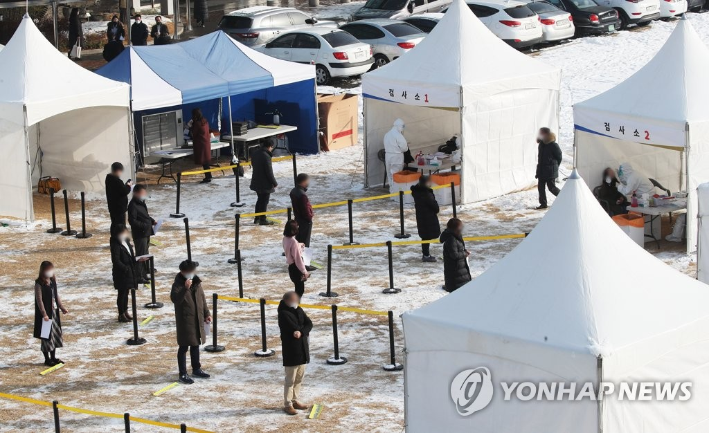 Visitors wait in line to receive COVID-19 tests at a makeshift clinic in Suwon, south of Seoul, on Jan. 13, 2021. (Yonhap)