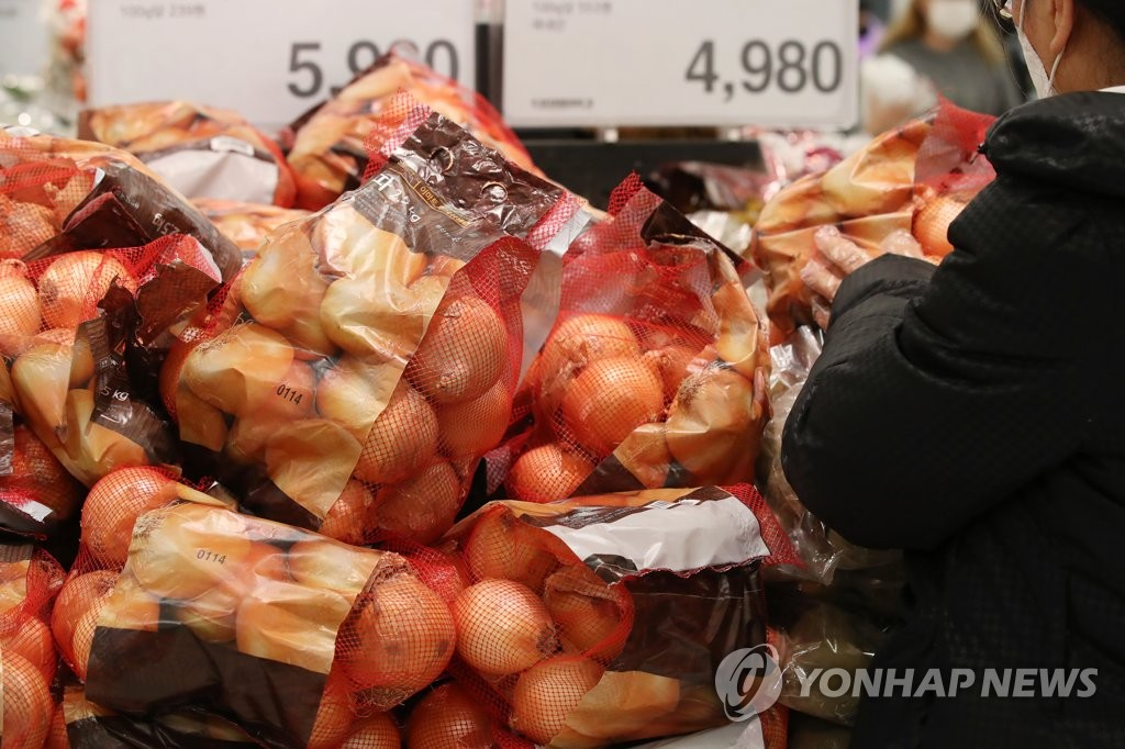 In this file photo, a shopper picks up a bag of onions at a supermarket in Seoul on Jan. 15, 2021. (Yonhap)