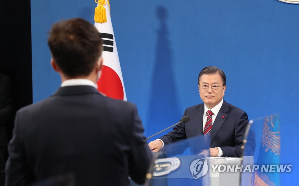 President Moon Jae-in (R) listens to a reporter's question during a New Year's press conference at the presidential office Cheong Wa Dae in Seoul on Jan. 18, 2021. (Yonhap)