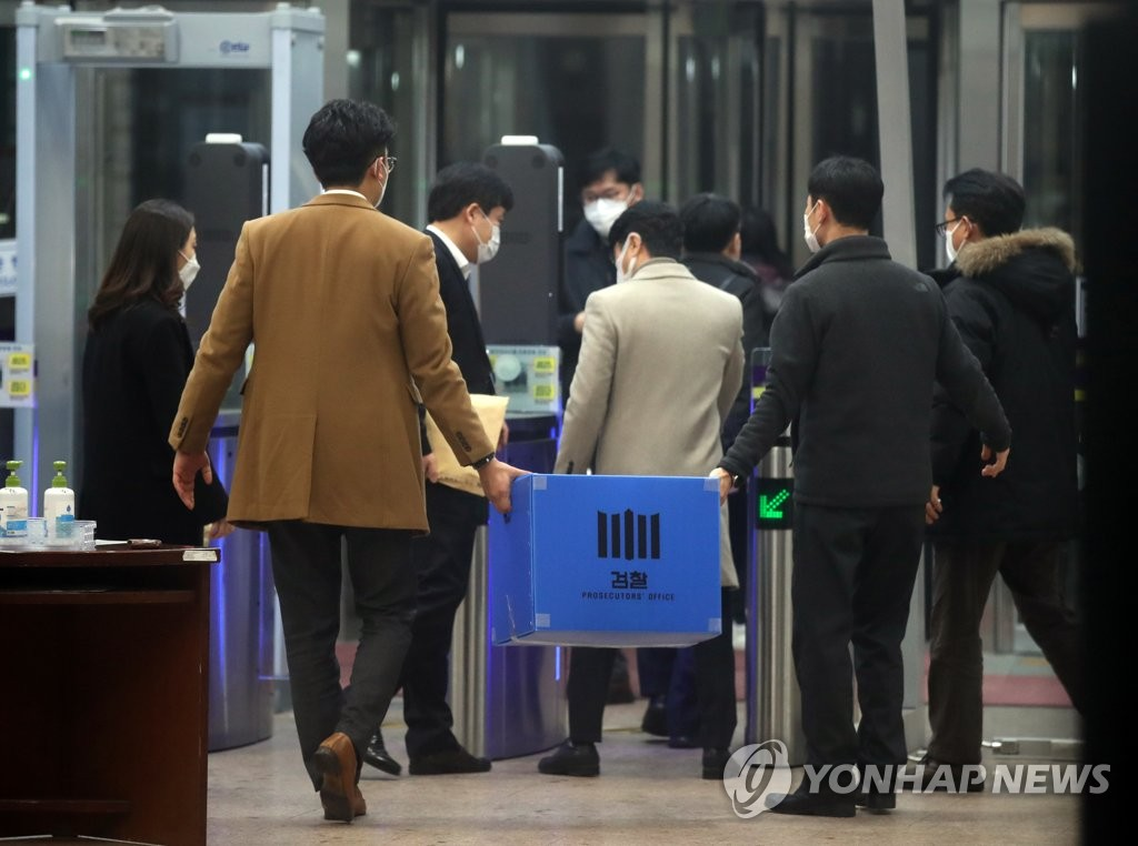 Prosecution investigators move a box of materials they seized during a search of the justice ministry in Gwacheon, south of Seoul, on Jan. 21, 2021, as part of investigation into an allegedly illegal travel ban on a former vice justice minister. (Yonhap)