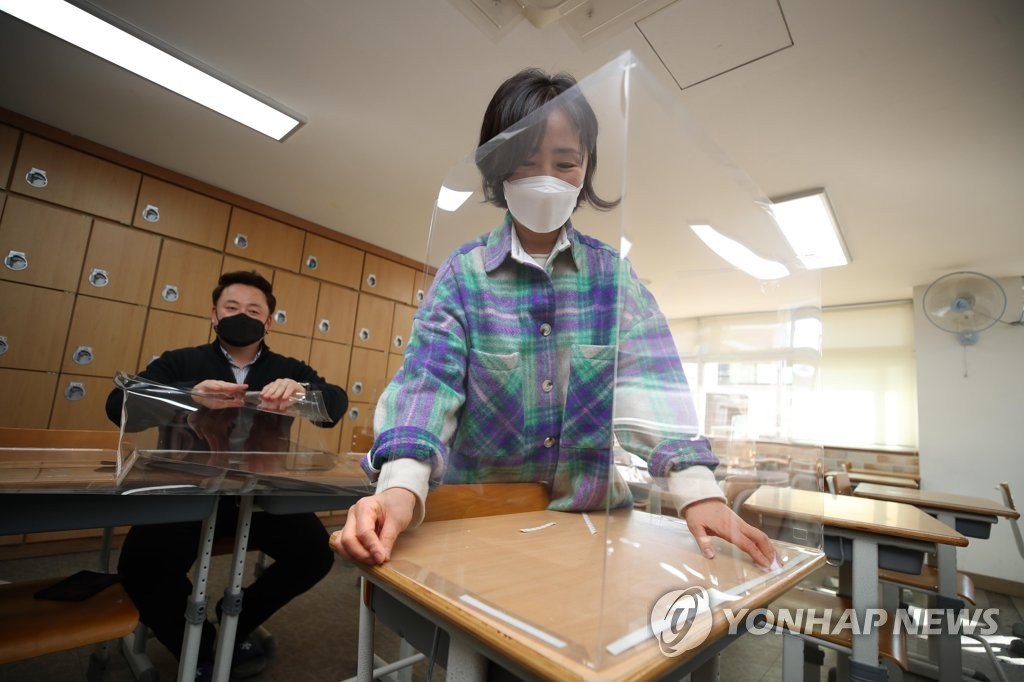 Teachers set up plastic partitions at a classroom in Daegu, 302 kilometers south of Seoul, on Feb. 23, 2021. (Yonhap)