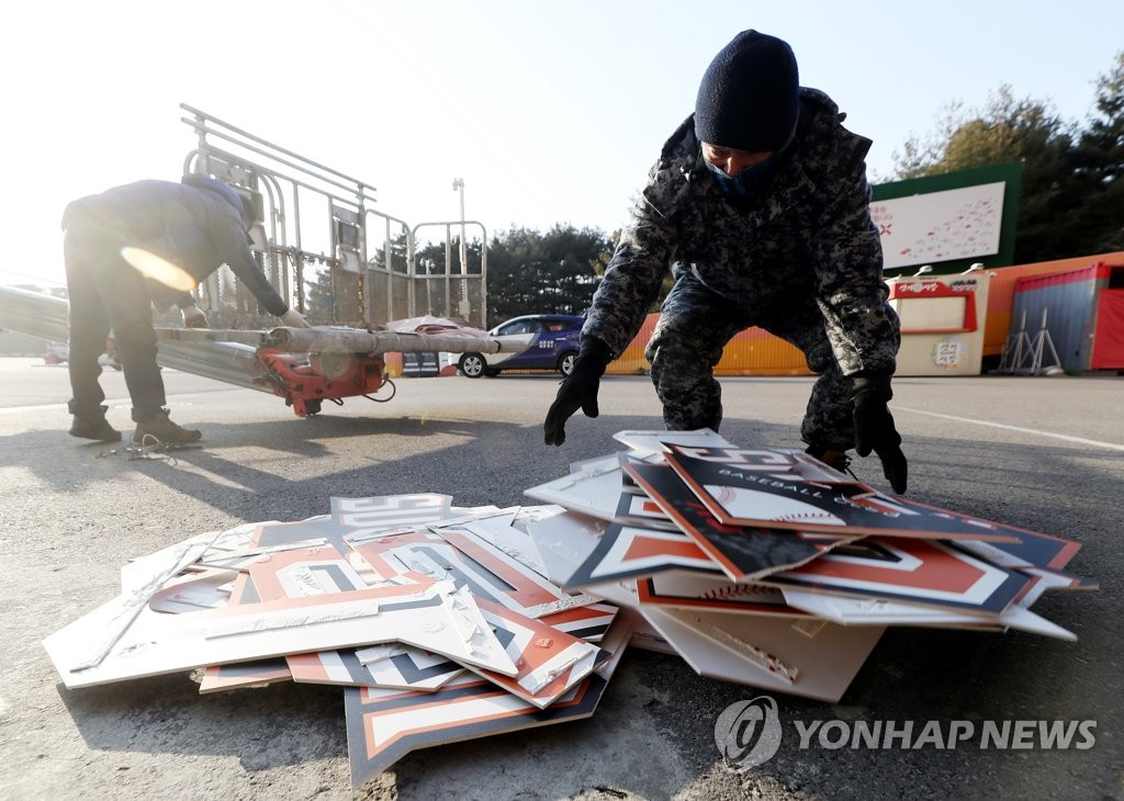 In this file photo from Feb. 23, 2021, workers pile up discarded signs for the SK Wyverns baseball club at SK Happy Dream Park in Incheon, 40 kilometers west of Seoul. (Yonhap)