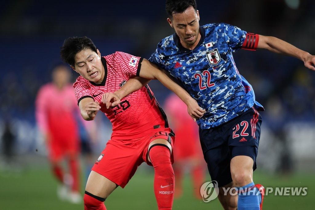 Lee Kang-in of South Korea (L) and Maya Yoshida of Japan battle for the ball during their friendly football match at Nissan Stadium in Yokohama, Japan, on March 25, 2021, in this photo provided by the Korea Football Association. (PHOTO NOT FOR SALE) (Yonhap)