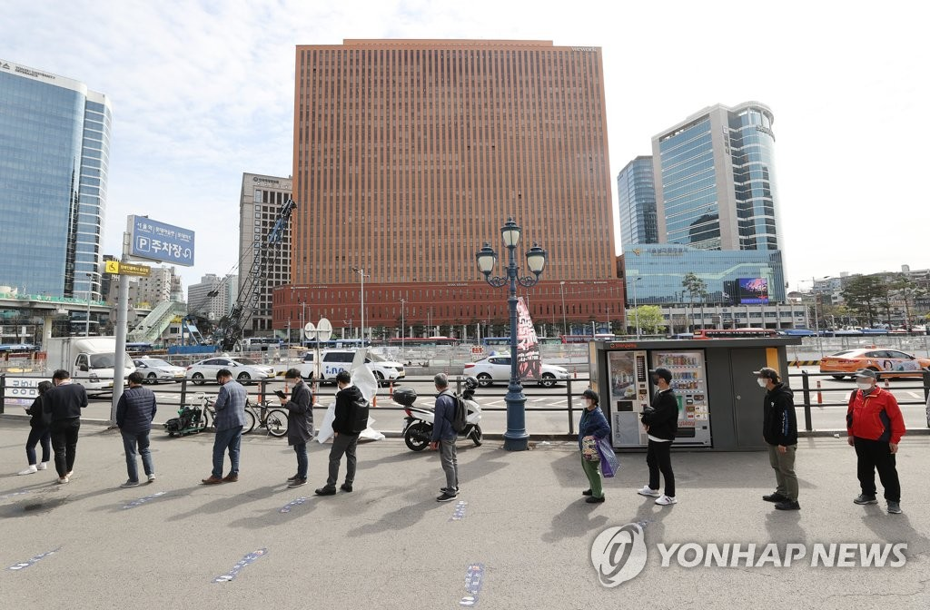 People stand in a line to receive COVID-19 tests at a makeshift clinic in central Seoul on April 2, 2021. (Yonhap)