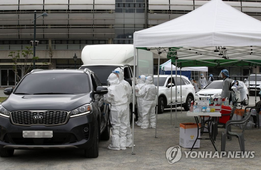 Medical staff conduct COVID-19 diagnostic tests at a drive-thru testing site in Damyang, 350 kilometers south of Seoul, on April 16, 2021. (Yonhap)