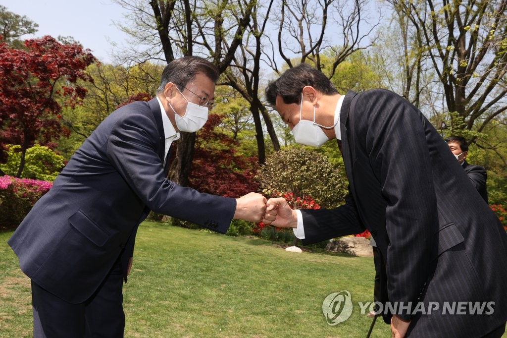 President Moon Jae-in (L) bumps fists with Seoul Mayor Oh Se-hoon at Cheong Wa Dae in Seoul on April 21, 2021. (Yonhap)