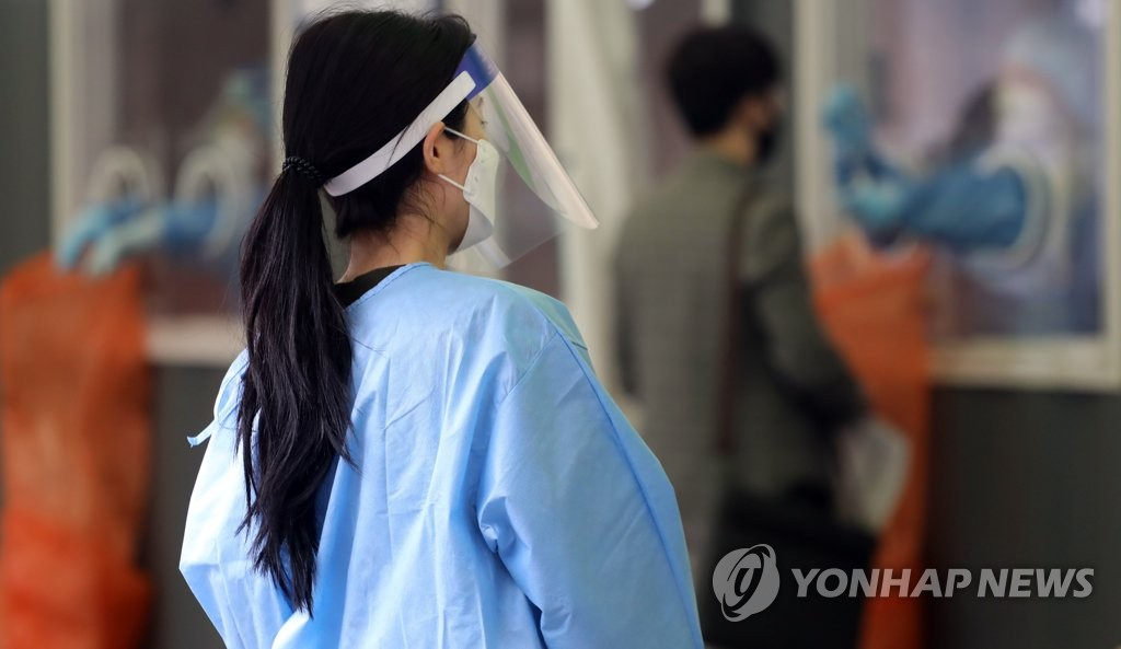 A health worker in a protective suit guides citizens at a makeshift virus clinic in Seoul on April 23, 2021. (Yonhap)