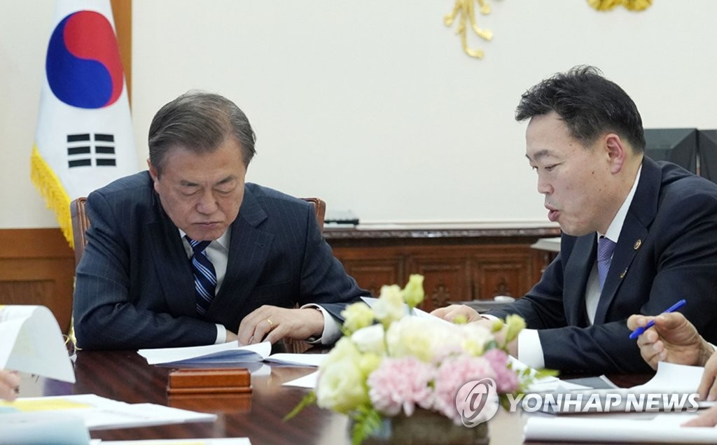 In this file photo dated Nov. 8, 2019, President Moon Jae-in (L) receives a report from then Vice Justice Minister Kim Oh-soo on prosecution reform plans at Cheong Wa Dae in Seoul. (Yonhap)