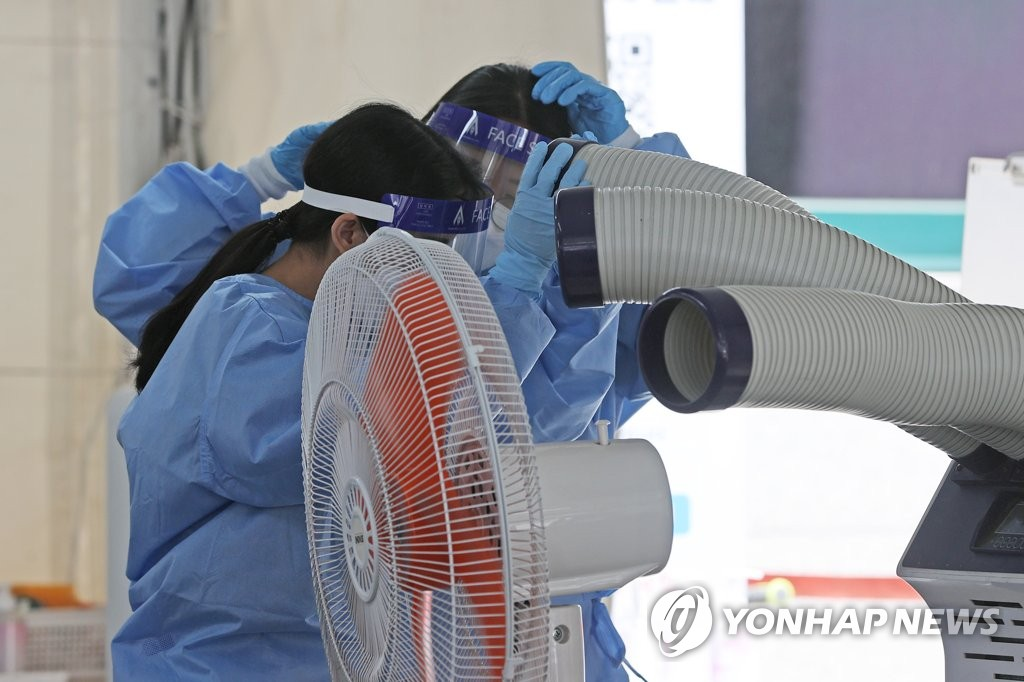 Medical workers place their heads in front of an evaporative air cooler at a COVID-19 test center in southern Seoul on May 19, 2021, amid early summer temperatures across the nation. (Yonhap)