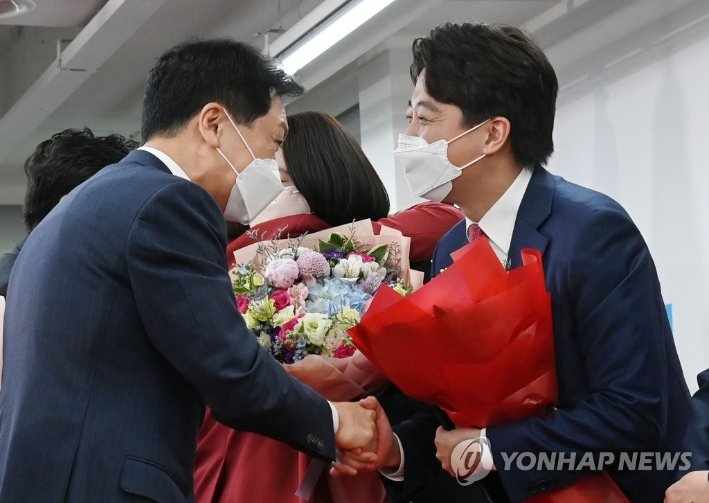Lee Jun-seok (R) of the main opposition People Power Party, shakes hands with floor leader Kim Gi-hyeon after being elected as the new chairman at the party headquarters in Seoul on June 11, 2021. (Yonhap)