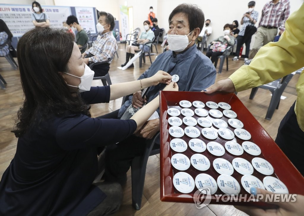 A public worker for the Jin Ward in Busan pins a vaccination badge on a city resident who completed his second-dose vaccination at a health care center in Busan, 453 kilometers southeast of Seoul, on June 16, 2021. (Yonhap)