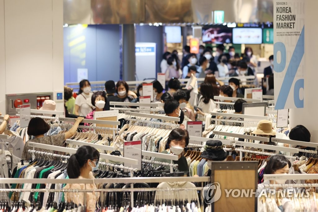 Citizens shop for clothes and shoes at a department store in southern Seoul as the fashion industry launched a sales festival on June 25, 2021. (Yonhap)