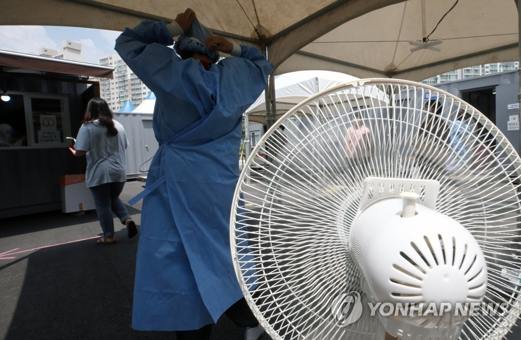 A medical worker stands next to a fan at a clinic in Gangneung, 237 kilometers east of Seoul, on July 16, 2021, amid the scorching summer heat. (Yonhap)