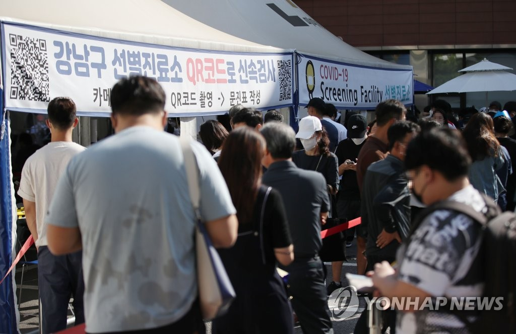 This photo taken Aug. 20, 2021, shows people waiting to receive a COVID-19 vaccine at a medical center in Gangnam, southern Seoul. (Yonhap)