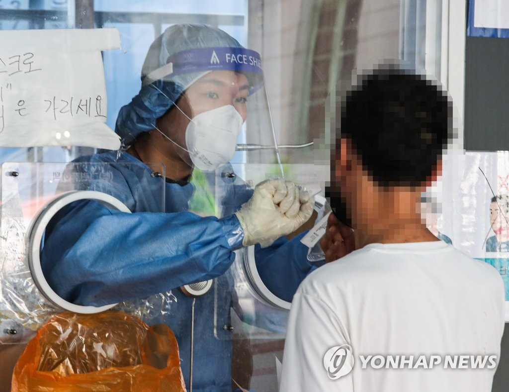 A medical worker collects a swab sample for a coronavirus test at a screening center in central Seoul on Sept. 3, 2021. (Yonhap)